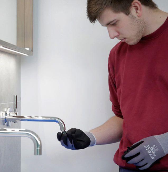Azubi an Waschtisch-Armatur bei Die Badgestalter