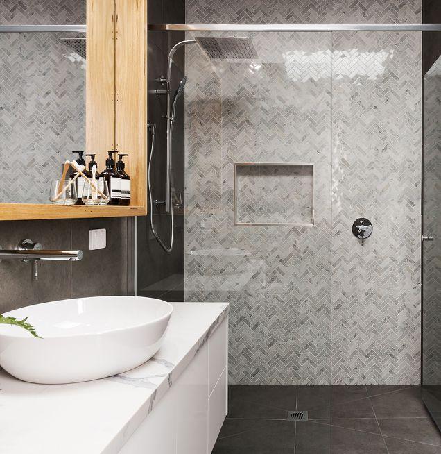 Duschwand mit Mosaikfliesen in diversen Grautönen