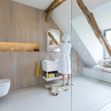 Frau im Badezimmer mit Dachschräge